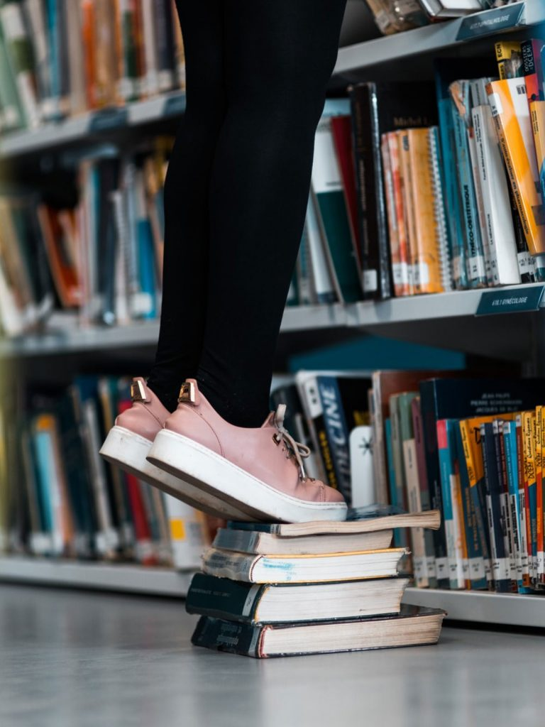 A person standing on books in library only showing lower legs and floor