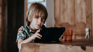 Improvisation with online therapy Thought Piece. A photo of a boy at a table looking at an iPad