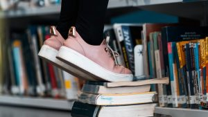 Psychoanalytic, Creative Curiosity and Constructive Skepticism Thought Piece. A person standing on books in library only showing lower legs and floor