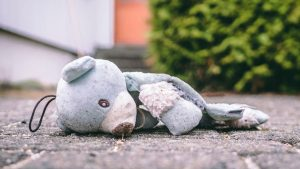 MINDinMIND Thought Piece on bullying feature image of a teddy lying on path outside a building