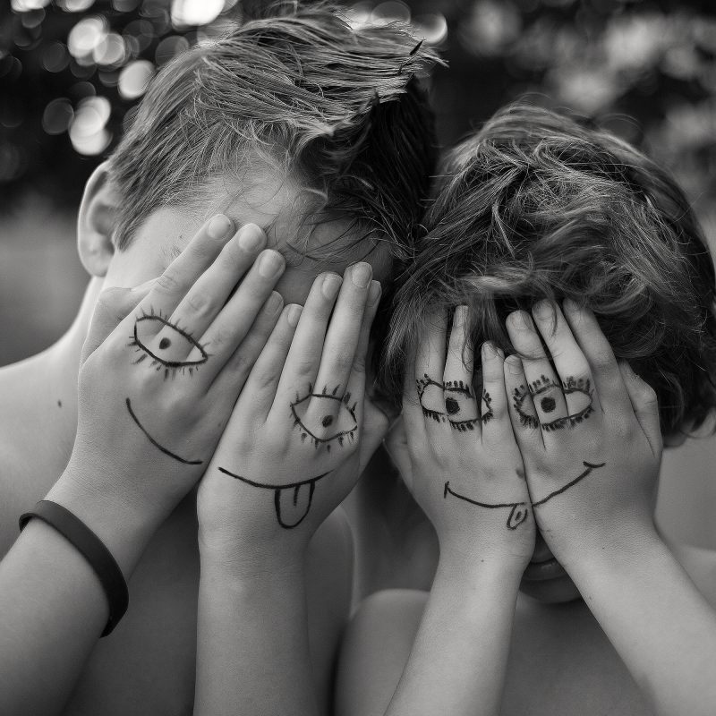 A photo of two boys with hands over face with drawings on their hands