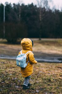 A young child walking away from the camera wearing an anorak and rucksack in the rain