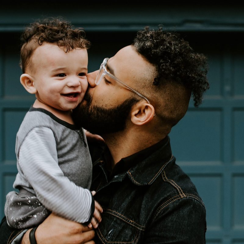 A photo of a father kissing the cheek of his young child