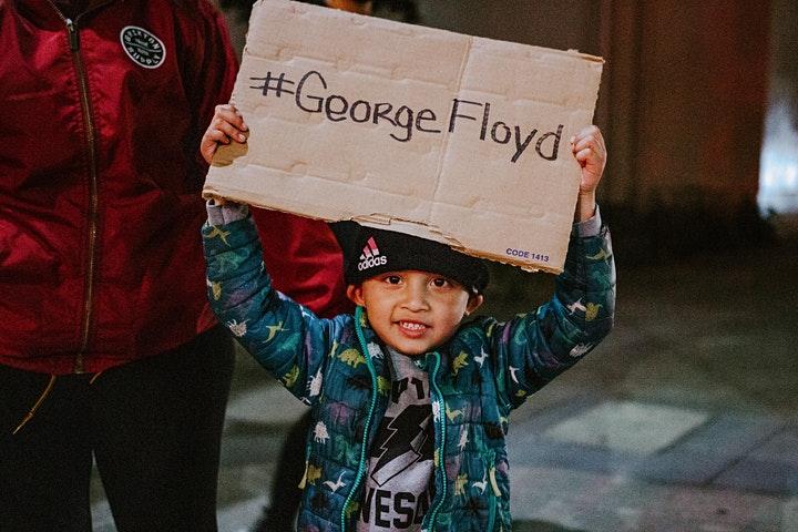 Boy holding George Floyd banner